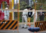 Workers of Tokyo's Toshima ward office carry container holding fragment of unknown object after it was dug up from the ground near playground equipment at a park in Toshima ward