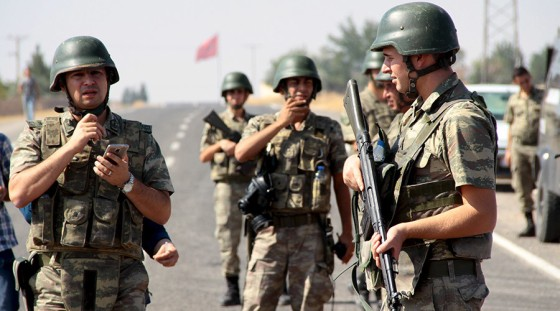 Turkish soldiers stand guard as a funeral convoy, carrying coffins of drowned Syrian migrants including the three-year old boy Aylan Kurdi, drives to the Turkish-Syrian border in Suruc, bordering with the northern Syrian town of Kobani, Turkey, September 4, 2015. Two Syrian toddlers who drowned with their mother as they were trying to reach Greece were laid to rest in the Syrian town of Kobani on Friday, a Reuters witness said. A photograph of the body of one of the toddlers, 3-year-old Aylan Kurdi, washed up on the shore, appeared in newspapers around the world this week, prompting sympathy and outrage at the perceived inaction of developed nations in helping refugees. REUTERS/Sertac Kayar - RTX1R28Z