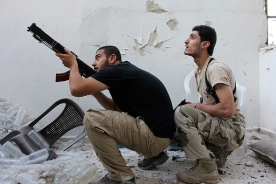 A Free Syrian Army fighter points his weapon as his fellow fighter watches in Aleppo's Al-Ezaa neighbourhood