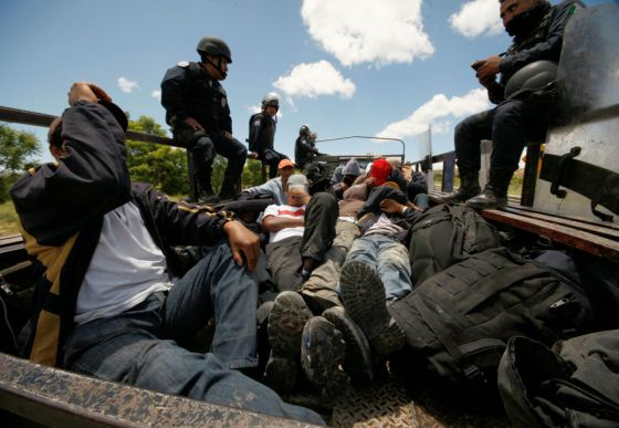 Riot police officers keep watch next to protesters from the National Coordination of Education Workers (CNTE) teachers' union who were detained after clashing with the police, in Nochixtlan