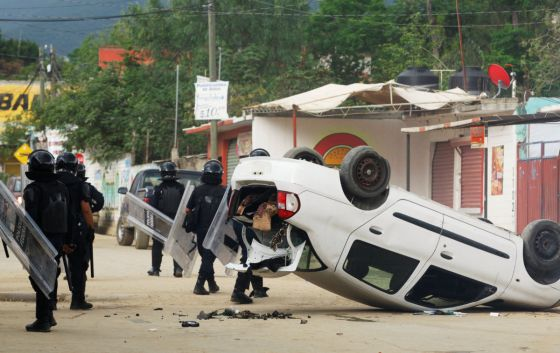 A riot police officers stand guard beside a damaged car after they clashed with protesters from the National Coordination of Education Workers (CNTE) teachers' union, in Nochixtlan